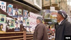Ethnic Kurds read campaign posters of candidates on a street in Irbil, in northern Iraq.