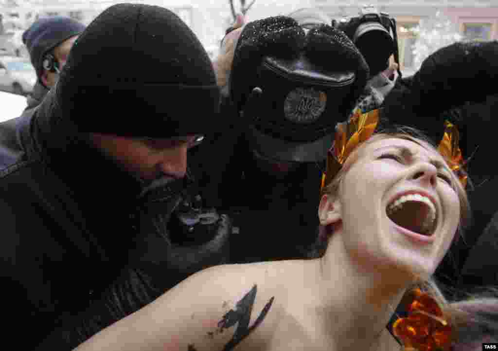Ukrainian police officers detain a topless Femen activist protesting against the untenability of the newly elected parliament in Kyiv. (ITAR-TASS/Maria Frolova)
