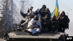 Ukrainian soldiers ride an armored personnel carrier as they leave the eastern Ukrainian city of Debaltseve on February 18.