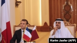 French President Emmanuel Macron (L) and Qatari Emir Sheikh Tamim bin Hamad al-Thani (R) watch as their foreign ministers sign bilateral agreements in the capital Doha, December 7, 2017