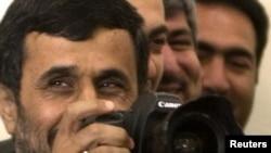 Прездент Ирана Махмуд Ахмадинежад с фотокамерой в руках после встречи глав МИД в Тегеране, 17 мая 2010 года