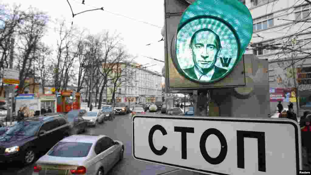 "A traffic light displays the image of Russian Prime Minister Vladimir Putin in Moscow on February 10. Images of Putin were stuck onto traffic lights in different parts of the city ahead of the presidential elections scheduled for March 4. The sign reads: ""Stop."" (Reuters/Sergei Karpukhin)"