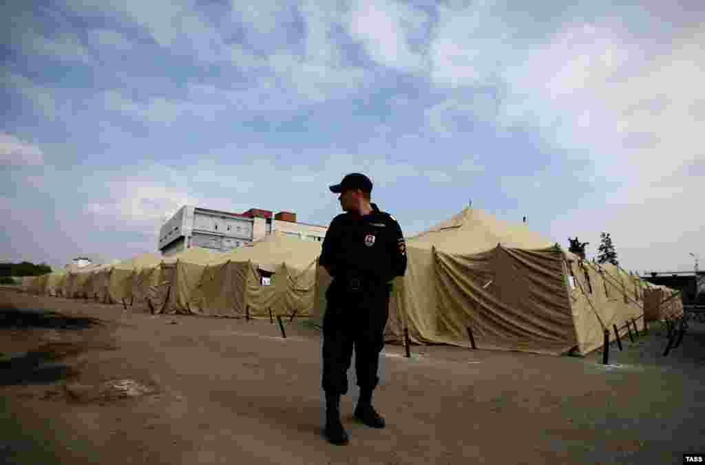 A Russian police officer stands guard at a tent camp for illegal migrant workers at the site of Moscow's former Cherkizovsky market in August. City authorities closed the market in 2009, alleging numerous illegal activities and safety violations.