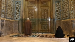 A cleric and a woman pray behind the closed door of Masoume Shrine in the city of Qom, some 80 miles (125 kilometers) south of the capital Tehran, Iran. March 16, 2020