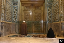 IRAN - A cleric and a woman pray behind a closed door of Masoume shrine in the city of Qom, some 80 miles (125 kilometers) south of the capital Tehran, Iran, Monday, March 16, 2020