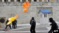 Greek riot police duck as a Molotov cocktail thrown by youths explodes in front of the parliament building in Athens on December 6, with a vote pending on the austerity budget.