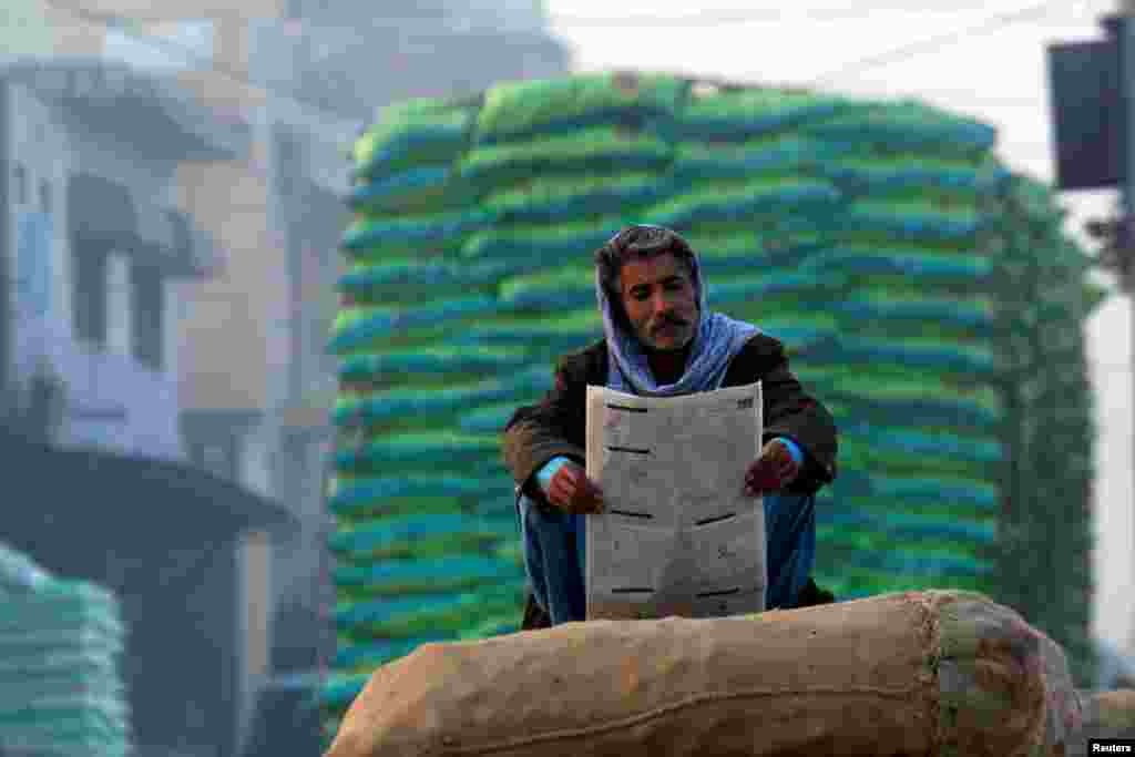 A man reads a newspaper while sitting on sacks of onions at a vegetable market in Islamabad, Pakistan. (Reuters/Faisal Mahmood)