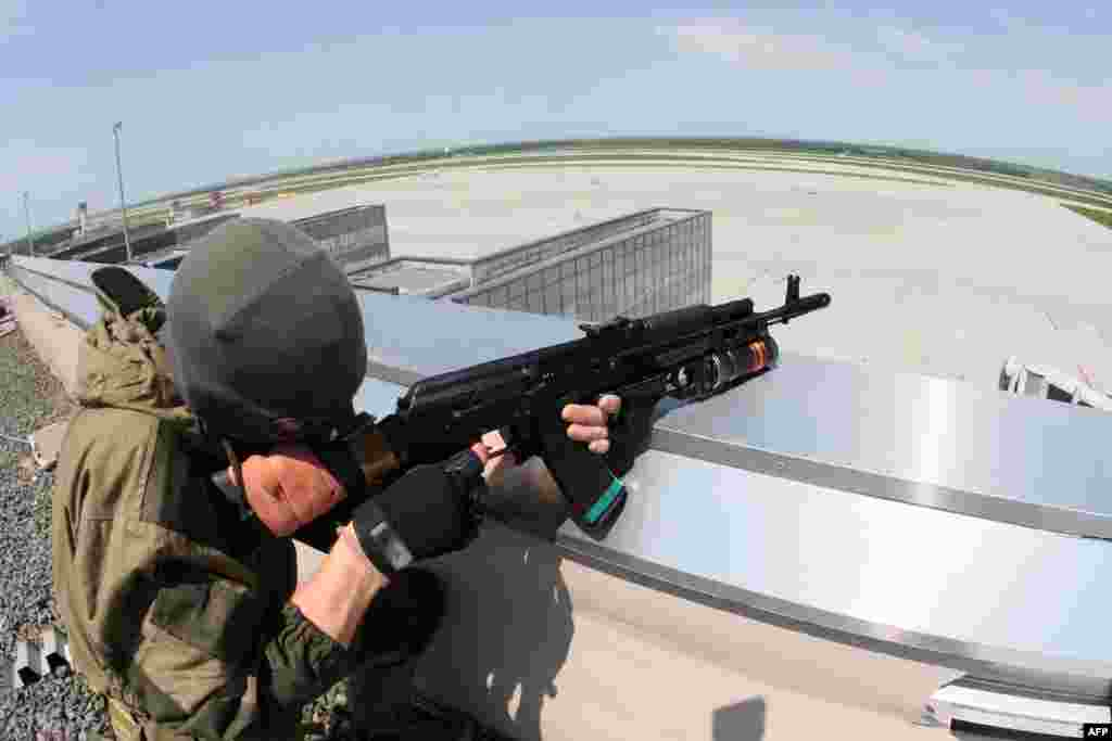 A pro-Russian militant takes up a position atop the Donetsk airport's roof.