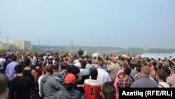 Җыелган халык митингта чыгыш ясаучыны тыңлый