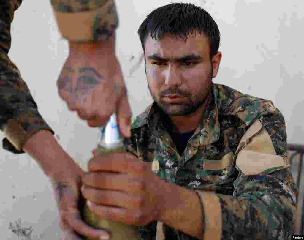 Syria -- A Kurdish fighter from the People's Protection Units (YPG) attaches a detonator to a rocket in Raqqa, June 15, 2017