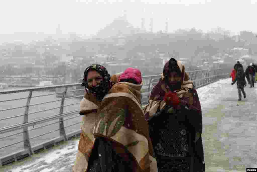 Syrian refugees brave the cold and snow as they walk to a metro station in Istanbul, Turkey, on February 11. (Reuters/Murad Sezer)