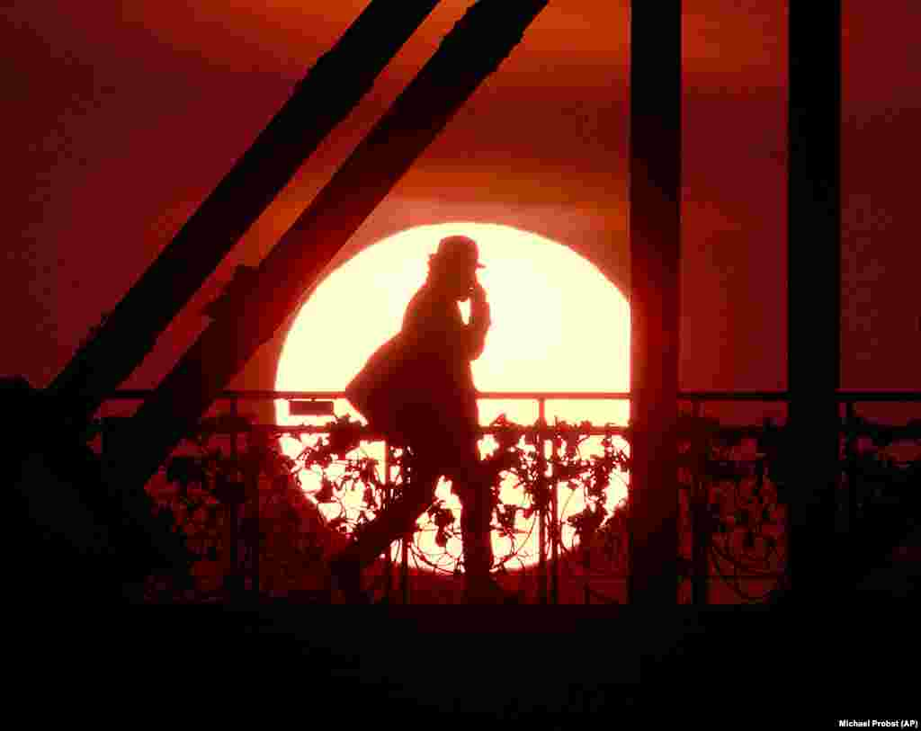 The sun rises behind the Eiserne Steg pedestrian bridge in Frankfurt, Germany, early on April 2. (AP/Michael Probst)