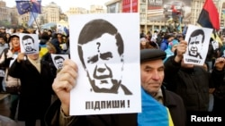 Protesters hold portraits of Ukrainian President Viktor Yanukovych during a demonstration in support of EU integration on Independence Square in Kyiv on November 29.