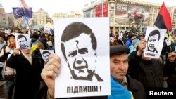 """Protestatari cu portretul lui Ianukovici şi inscripţia """"Semnează!"""""""