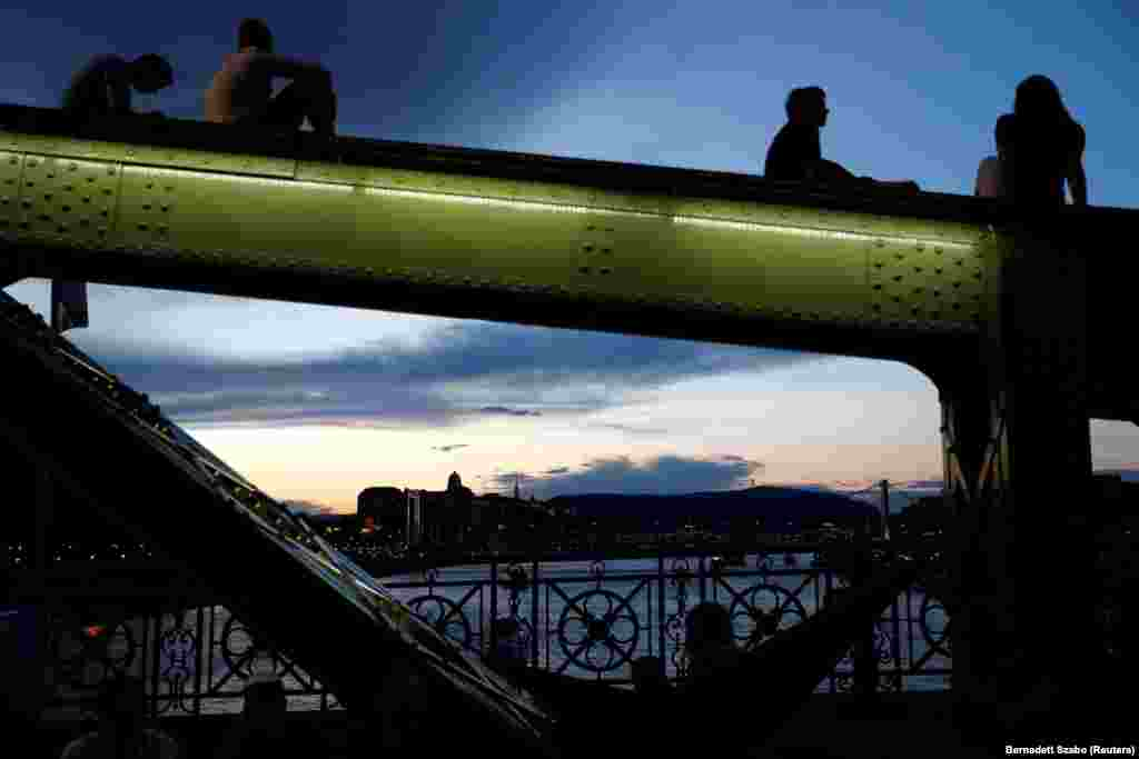 Buda Castle is seen in the background as people sit on Liberty Bridge in Budapest, Hungary. (Reuters/Bernadett Szabo)