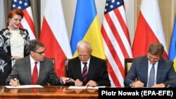 U.S. Energy Secretary Rick Perry (left to right), Polish energy official Piotr Naimski, and Ukrainian National Security and Defense Council chief Oleksandr Danylyuk sign an accord in Warsaw on August 31.