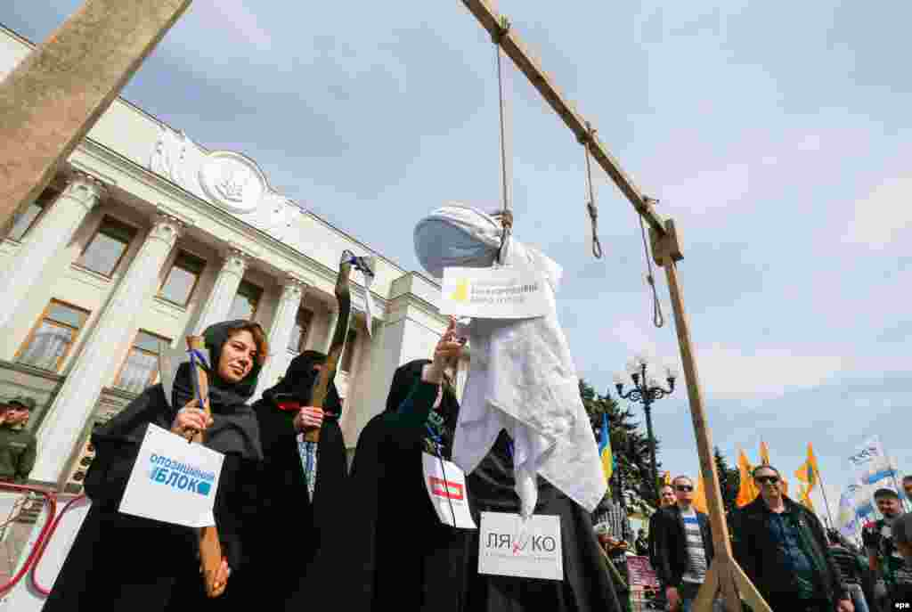 "Activists wearing symbolic executioner's clothes hang an effigy with a sign reading ""National Anticorruption Bureau of Ukraine"" during a protest at parliament in Kyiv on May 16. (epa/Serhiy Dolzhenko)"
