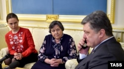 Президент Украины Петр Порошенко разговаривает по телефону с военнослужащей Надеждой Савченко, рядом с ним мать Мария и сестра Вера бывшего пилота. Киев, 19 апреля 2016 года.