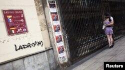 Par gleda izlog zatvorene trgovine pored zida sa kursnom listom i grafiom 'lopovi', Madrid, juni 2012.