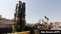 People take a picture next to a Russian-made S-300 air defense system displayed on Baharestan square in Tehran, September 24, 2017