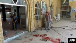 Irak - Disa njerëz duke pastruar pas shpërthimit të një bombe në xhaminë e Shiitëve