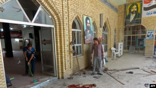 Men clean up after a bomb detonated at a Shi'ite mosque in the northern city of Kirkuk on April 19.