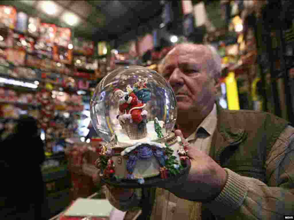 A man inspects a Santa Claus snowglobe in a Christmas shop in Tehran. - Photo by Mehr