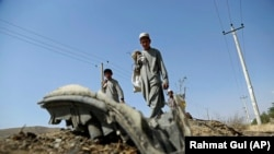 Afghan boys look at the debris of suicide attacker's vehicle in Kabul on July 24.