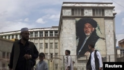 Afghans in Kabul walk past a picture of President Hamid Karzai, who is seeking support at the jirga for his plans to reach out to some Taliban militants.