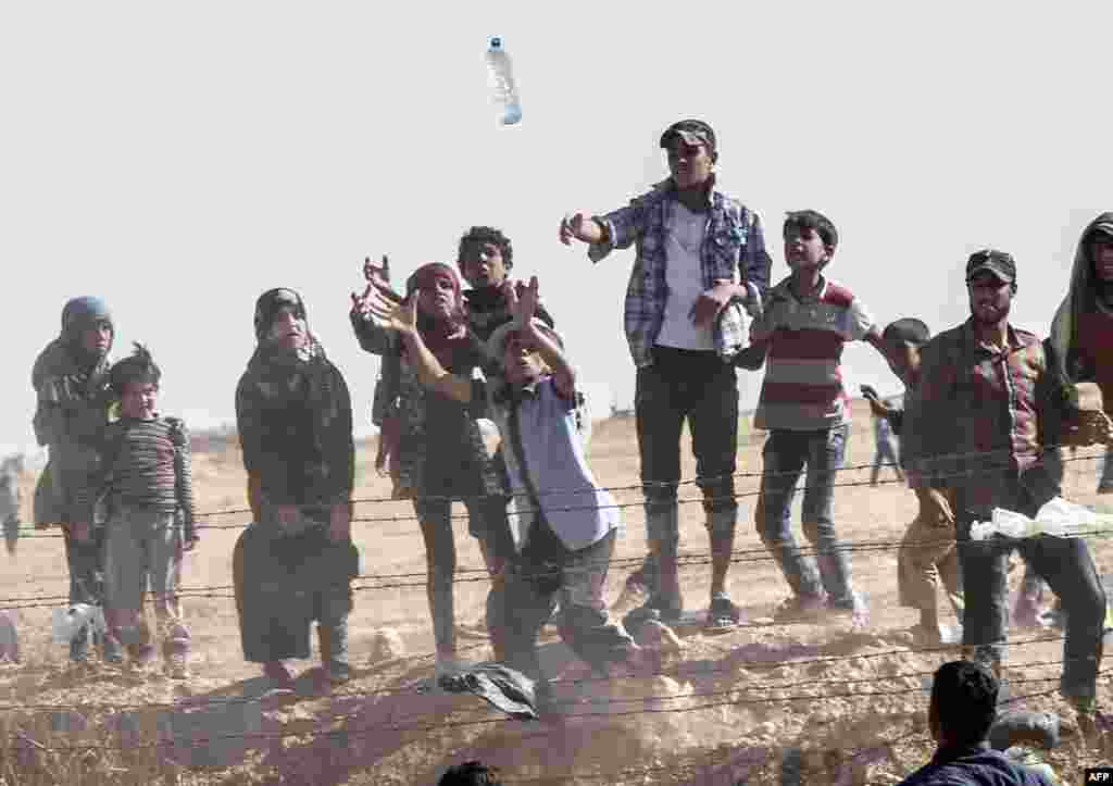 Syrian refugees try to grab bottles of water thrown from the Turkish side of the border near the Syrian town of Tal Abyad, at Akcakale in Sanliurfa Province. (AFP/Bulent Kilic)