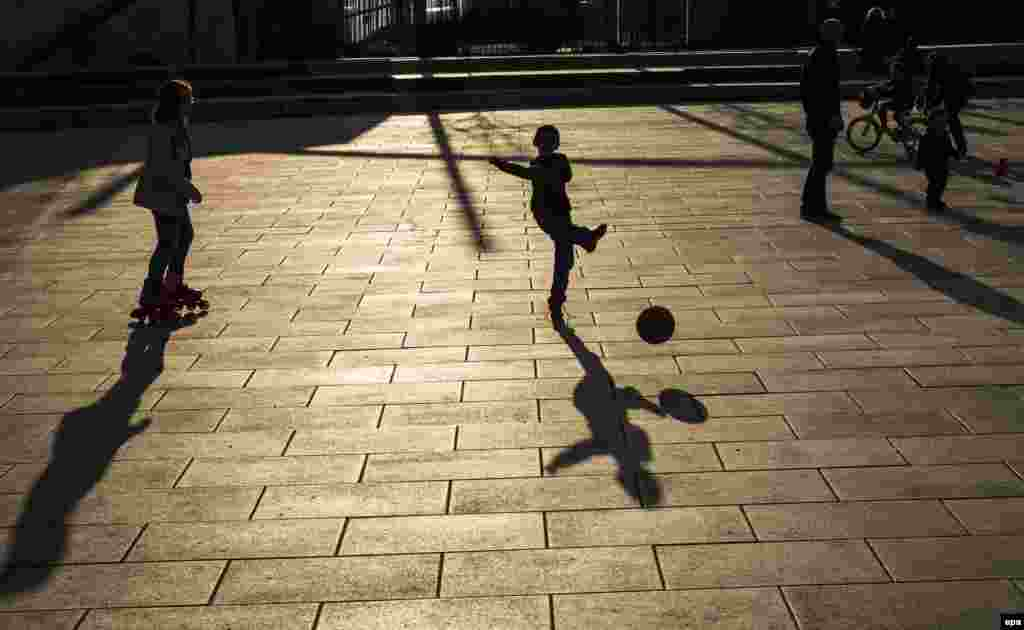 Children play as the sun sets on a public square in Pristina, Kosovo, on March 21. (AFP/Sergei Gapon)