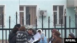 Бывшие рабочие сахарного завода стоят в ожидании решения перед зданием районного суда. Карабулак, 26 ноября 2009 года.