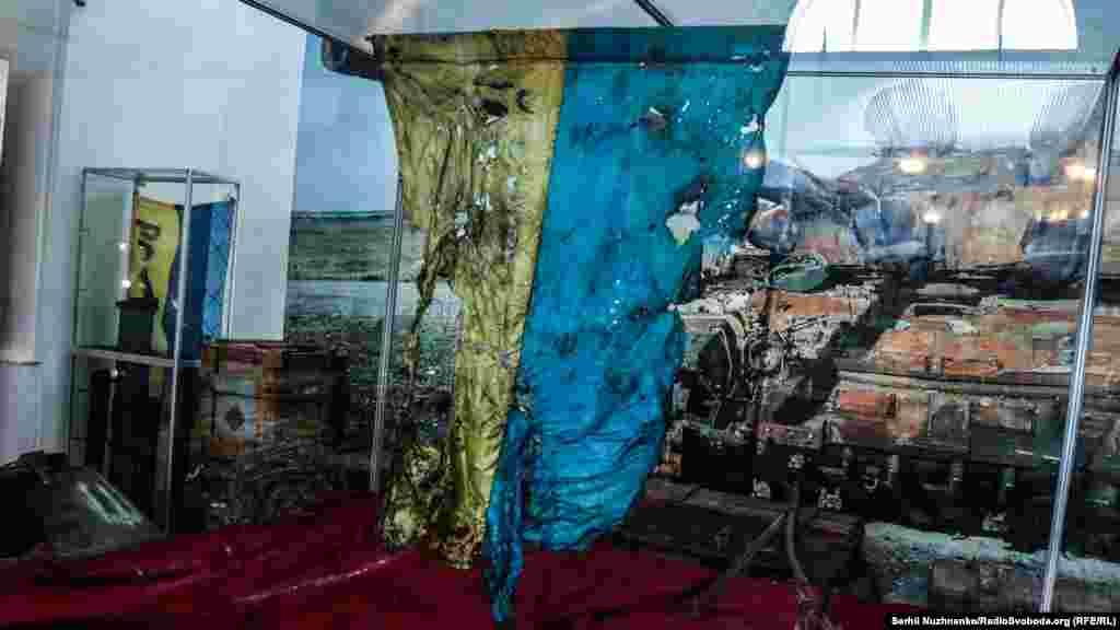 Государственный флаг Украины из «Иловайского котла». Флаг принадлежал бойцу 93-й отдельной механизированной бригады Александру Куренко. Флаг он получил в подарок от друга перед ротацией в зону АТО. Изуродованный флаг нашли в сгоревшей машине ЗИЛ во время поиска тел погибших