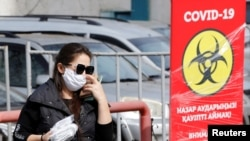 Женщина в защитной маске у пункта тестирования в Алматы во время пандемии нового коронавируса.