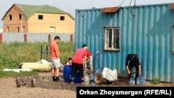 Астана қаласының маңындағы Қоянды ауылында сатылатын су кезегінде тұрған адамдар. Ақмола облысы, 6 тамыз 2013 жыл. (Көрнекі сурет)