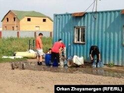 Местные жители набирают воду. Село Коянды, 6 августа 2013 года.