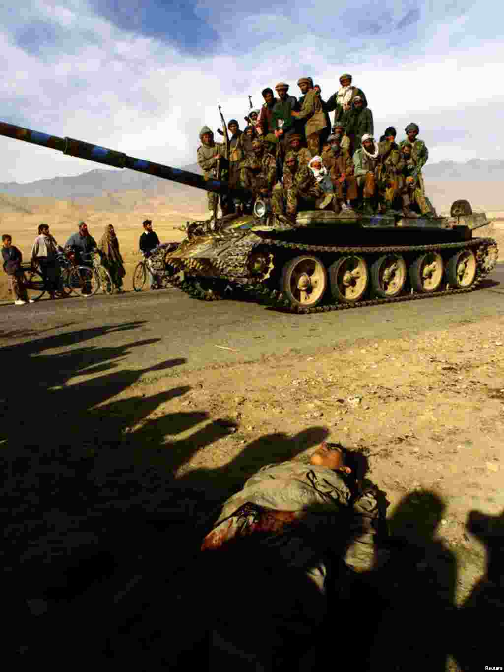 Northern Alliance fighters ride on a T-62 tank past a dead body on the motorway 3 km north of Kabul, as Northern Alliance fighters approached the Afghan capital, November 13, 2001. Forces of the anti-Taliban Northern Alliance entered Kabul on Tuesday after Taliban forces fled the capital, and were greeted by civilians. REUTERS