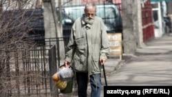 Таяқ ұстаған ер адам көшеде кетіп барады. Көрнекі сурет