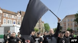 Followers of Germany's neo-Nazi NPD party wave a black flag during May Day demonstrations in Berlin's Koepenick district on May 1, 2009.
