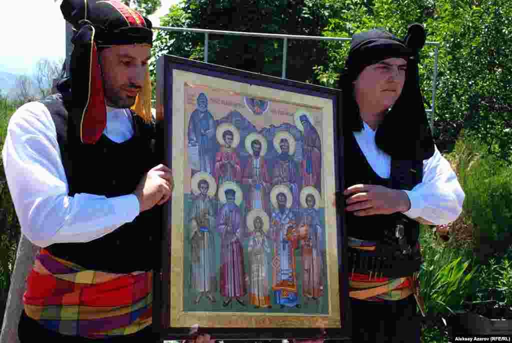 Два молодых человека несут большую икону. Они одеты в одежду, традиционную для понтийских греков, непосредственных предков местных греков.