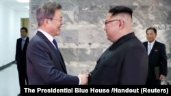 South Korean President Moon Jae-in (left) shakes hands with North Korean leader Kim Jong Un during their summit in the truce village of Panmunjom, North Korea, in this handout picture provided by Seoul's Presidential Blue House on May 26.