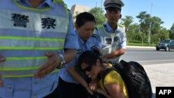 Поліція Китаю відбирає камеру у журналістки в місті Лукцюнь, де днями пройшли перші заворушення, в Сіньцзян-Уйгурському автономному районі, 28 червня 2013 року