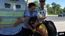 Китайские полицейские забирают фотоаппарат у журналиста в городе Луккун в Синьзяне. 28 июня 2013 года. Иллюстративное фото.