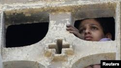 Момче гледа од прозорецот на црквата Св. Марија што беше запалена во судирите меѓу муслиманите и христијаните во саботата