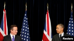 Belgium -- US President Barack Obama (R) and British Prime Minister David Cameron look at each other as they speak at a joint news conference after their meeting at the G7 summit in Brussels, June 5, 2014