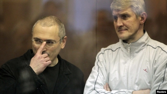 Jailed Russian former oil tycoon Mikhail Khodorkovsky (left) and his business partner Platon Lebedev stand in the defendants' cage before the start of a court session in Moscow in 2010.