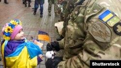 Девочка дает игрушку украинскому военному из батальона «Киев-12». Киев, 6 декабря 2014 года
