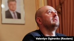 "Russian dissident journalist Arkady Babchenko, whose name was not on the alleged ""Russian hit list,"" speaks to the media on May 31 following his faked death, as a portrait of President Petro Poroshenko hangs on the wall behind him."
