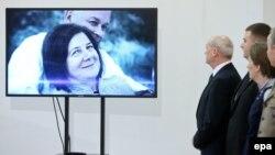 Министр обороны Польши Антони Мачеревич смотрит на экран, где изображены Лех Качиньский и его супруга Мария во время церемонии, на которой было объявлено о возобновлении расследования катастрофы под Смоленском