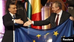 Hungarian Prime Minister Viktor Orban (left) and Belgian Prime Minister Yves Leterme hold the European flag at the Presidency handover ceremony in Budapest on January 6.